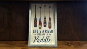 """Image of a """"Life's A River Grab A Paddle"""" Sign"""
